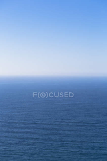 Pacific Ocean calm water merging into blue sky. — Stock Photo