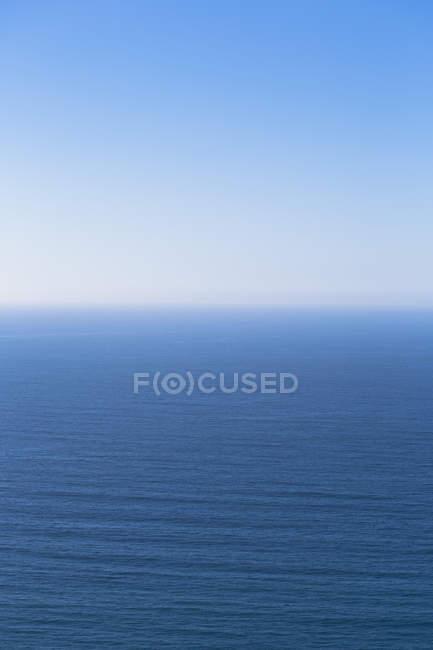 Тихий океан спокійна вода зливаються в Синє небо. — стокове фото