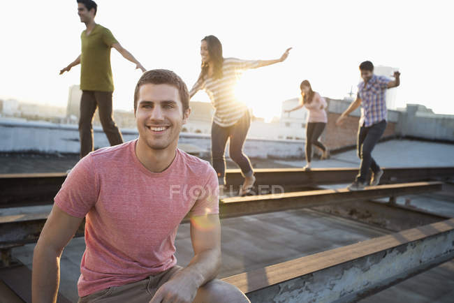 Man sitting in front of group of people at dusk balancing and walking along steel struts on rooftop. — Stock Photo