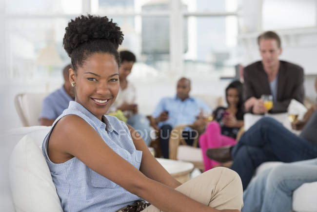 Mid adult woman smiling and looking in camera with people having party in background. — Stock Photo