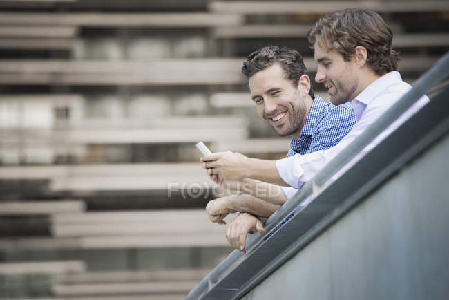 Two men leaning on railing, using smartphone and smiling in street. — Stock Photo