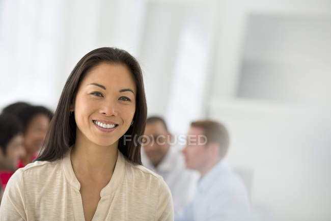 Confident businesswoman standing in meeting room with colleagues in background. — Stock Photo
