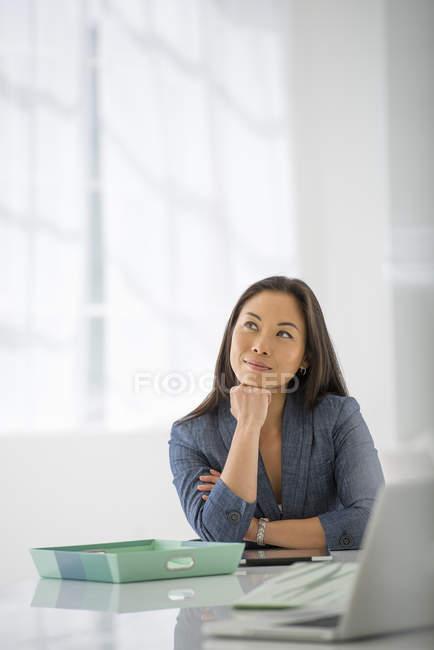 Жінка з руки на Хін розслабляючий в офісному столі з ноутбук і зелений папки. — стокове фото