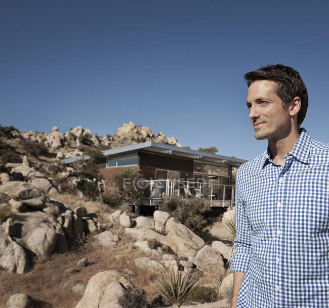 Man standing in front of house on rocky hillside of desert landscape. — Stock Photo