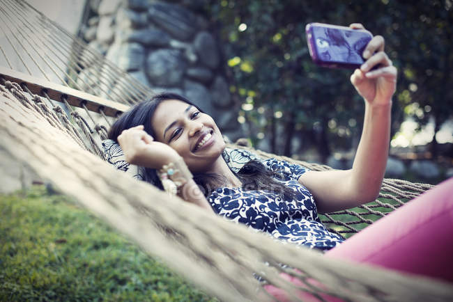 Woman lying in garden hammock and taking selfie with phone. — Stock Photo