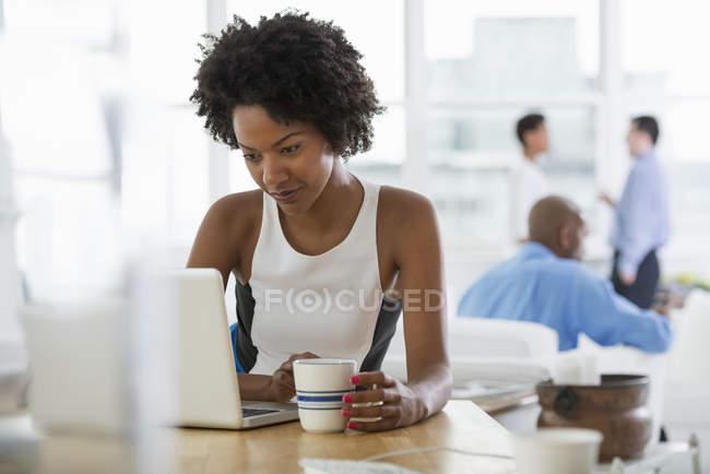 Женщина с ноутбуком на столе и проведение чашки в офисе на рабочем месте с коллегами в фоновом режиме . — стоковое фото