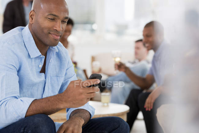 Man using smartphone with people having party in background. — Stock Photo