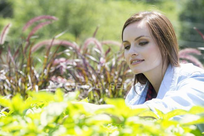 Jovem mulher no jardim examinando o cultivo de plantas. — Fotografia de Stock