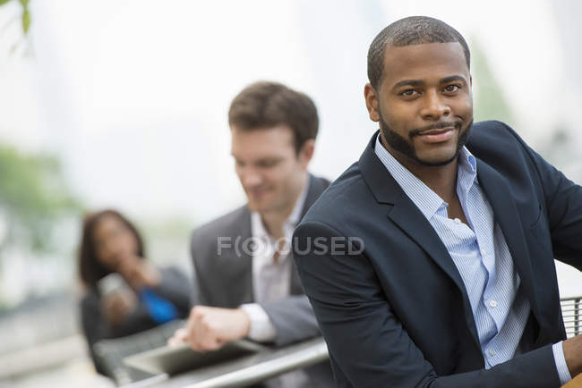 Businessman leaning on railing and looking in camera with colleagues on city street. — Stock Photo
