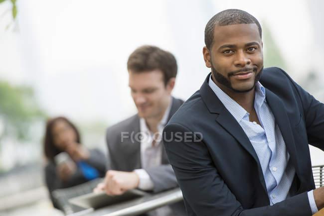 Uomo d'affari che si appoggia sulla ringhiera e guardando a porte chiuse con i colleghi sulla strada della città — Foto stock