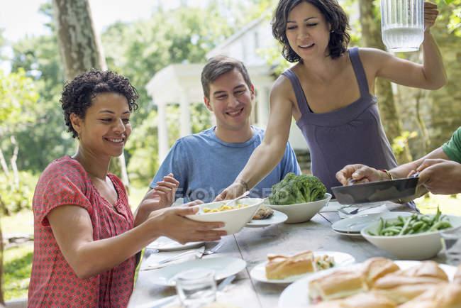 Друзья и семья собираются за обеденным столом в сельском саду . — стоковое фото