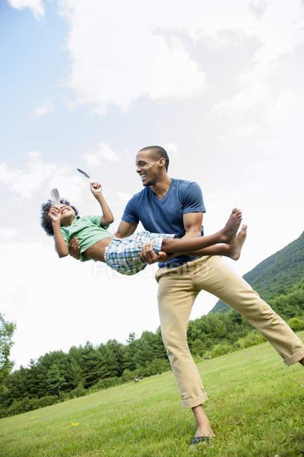 Mann, Sohn in Arme heben, beim Spielen im freien — Stockfoto