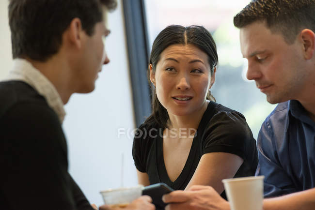 Group of friends sitting around table in coffee shop with drinks and using digital tablet. — Stock Photo