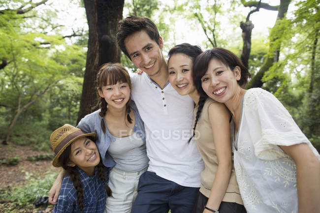 Group of Japanese friends posing and embracing in forest. — Stock Photo