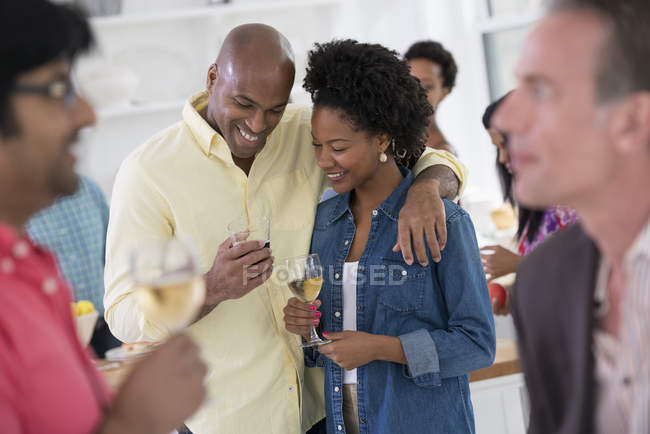 Man and woman smiling and embracing with glasses and people at party. — Stock Photo