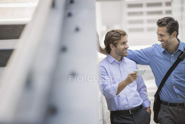 Two businessmen standing in urban street and using smartphone. — Stock Photo