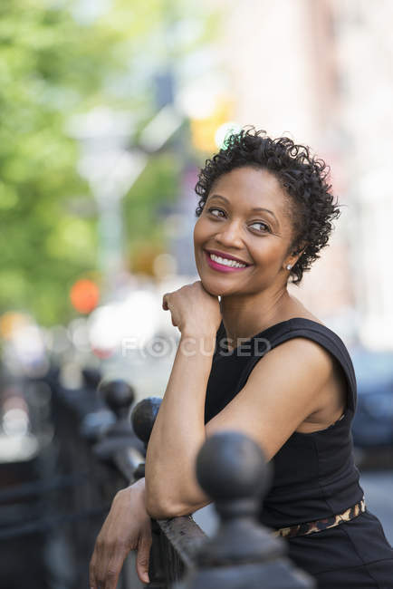 Woman in black dress leaning on railing on city street. — Stock Photo