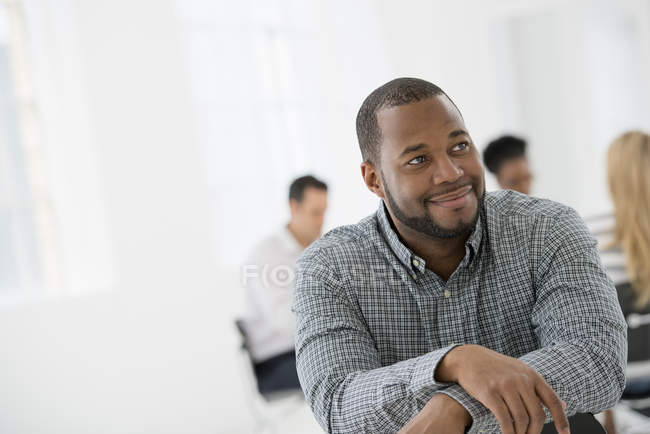 Mid adult man sitting separately from group of people at business meeting in office. — Stock Photo