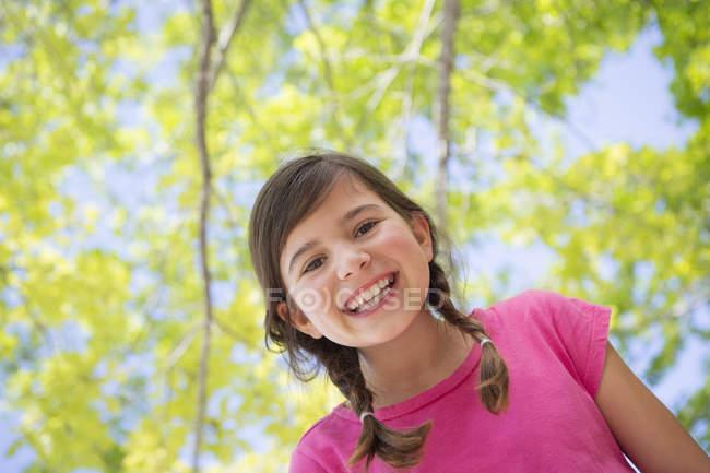 Mädchen im Grundalter mit Zöpfen unter Baumkronen, Portrait. — Stockfoto
