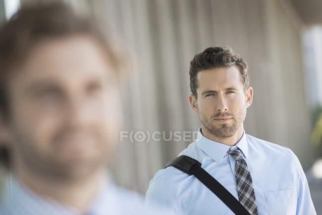 Два предпринимателя, стоя на улице с упором на фоне — стоковое фото