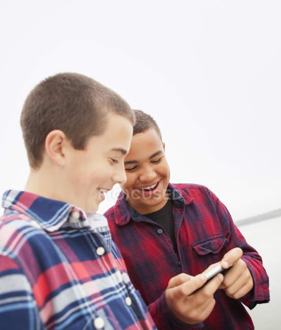 Teen boys looking down at phone screen on lake shore. — Stock Photo