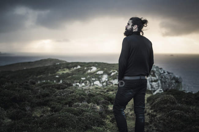 Man with beard and hair bun standing and looking over mountain landscape at sunset. — Stock Photo