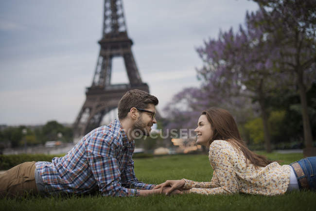 Couple lying on grass and holding hands under shadow of Eiffel Tower in Paris, France. — Stock Photo