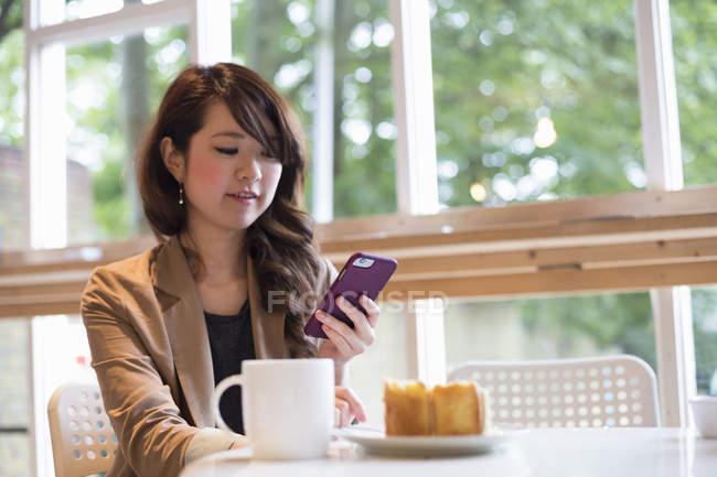Mujer joven sentada en la mesa con taza y rebanada de pastel y usando un teléfono inteligente . - foto de stock