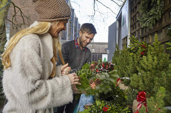 Femme en manteau de fourrure et homme choisissant traditionnelles couronnes de Noël au marché — Photo de stock
