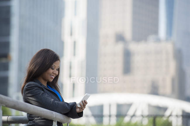 Businesswoman in grey suit using smartphone in city downtown. — Stock Photo