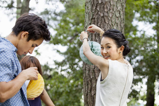 Japanese friends hanging lanterns for party in woods. — Stock Photo