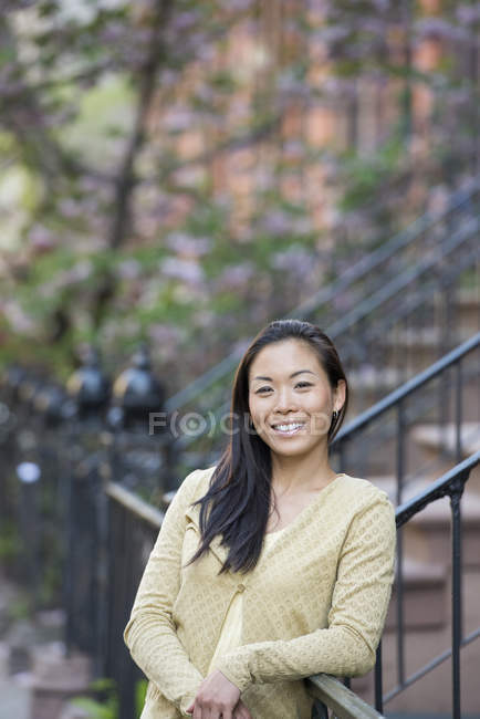 Mid adult woman with long black hair leaning on railing of building steps. — Stock Photo