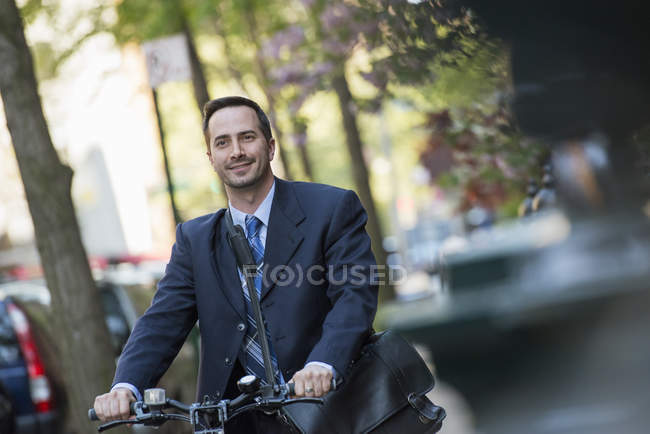 Man in business suit sitting on bicycle with bag on street. — Stock Photo