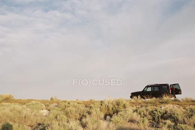 Жінка, стоячи відкрити задні двері транспортного засобу в поле. — стокове фото