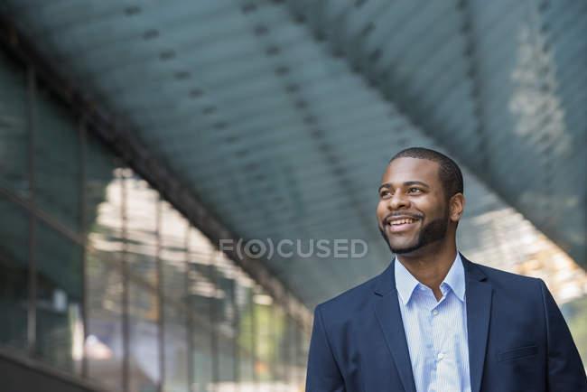 Homme d'affaires veste bleue debout devant un immeuble de bureaux moderne . — Photo de stock