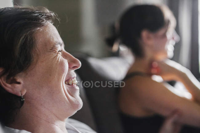 Two women in profile sitting indoors and laughing. — Stock Photo
