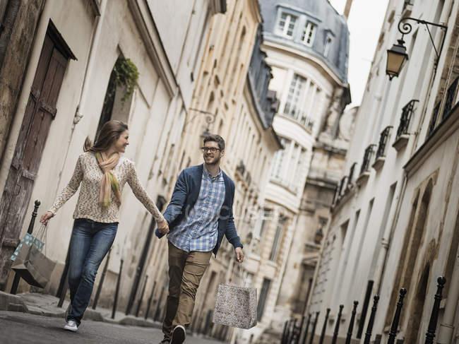 Couple marchant le long d'une rue étroite en ville historique avec des sacs à provisions — Photo de stock
