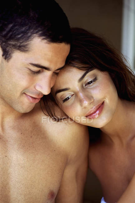 Young topless man and woman smiling and cuddling indoors. — Stock Photo