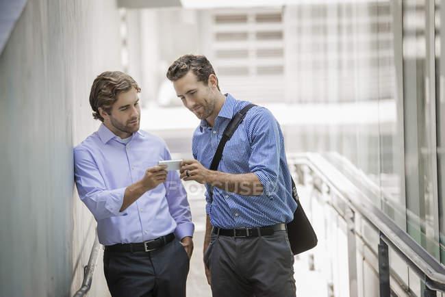 Dois homens de negócios, em pé na rua urbana e compartilhamento de smartphone — Fotografia de Stock