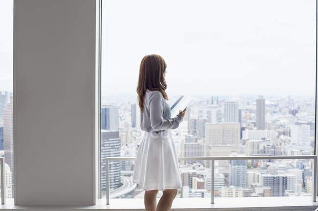 Donna in possesso di file e guardando la vista in edificio per uffici . — Foto stock