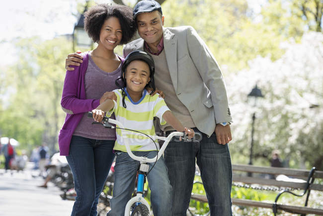Portrait of happy family with boy with bicycle in sunny park. — Stock Photo