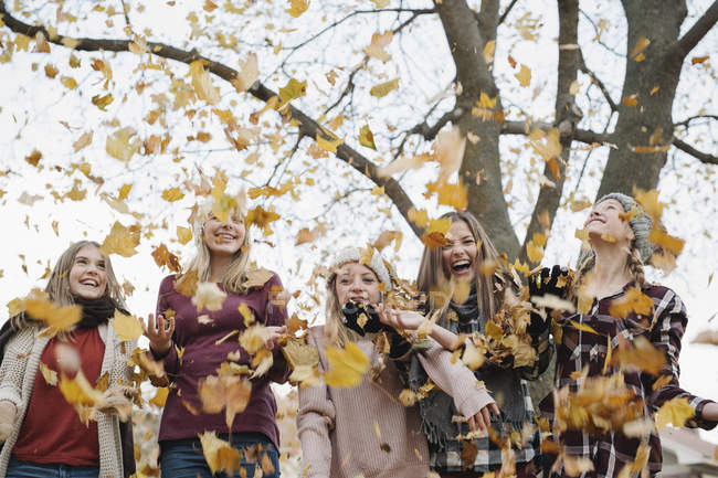 Five teenage girls in woolly hats and scarves throwing autumnal leaves in air. — Stock Photo