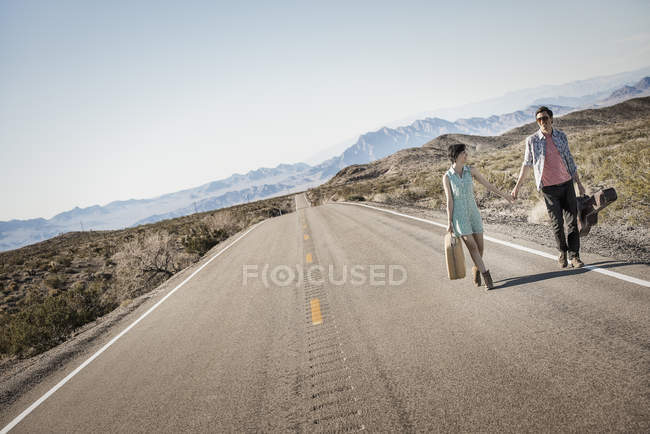 Young couple walking hand in hand and carrying cases on tarmac road in desert. — Stock Photo