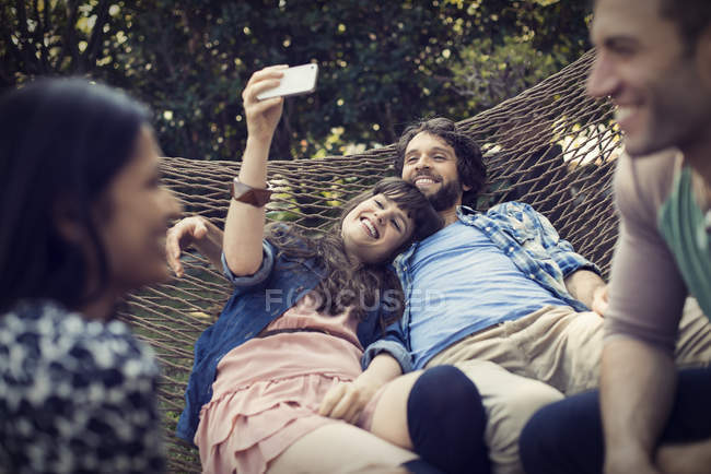 Group of cheerful friends lounging in hammock in garden, talking and taking selfie. — Stock Photo