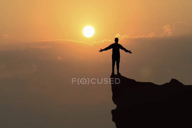 Mann, stehend auf Felsen bei Sonnenuntergang mit ausgestreckten Armen — Stockfoto