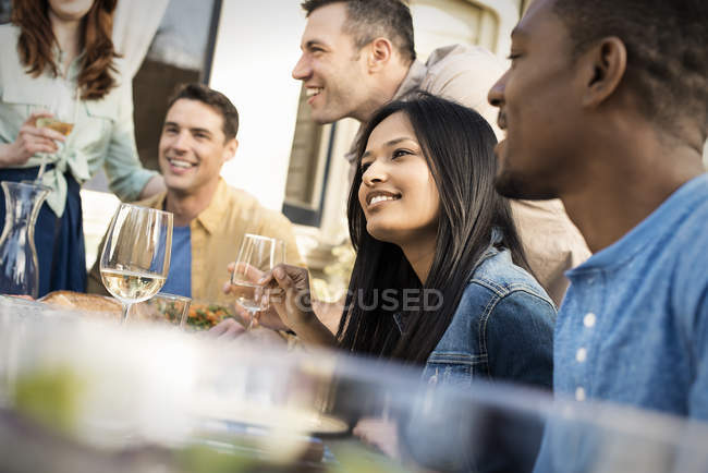 Group of men and women gathering around table and having drinks. — Stock Photo