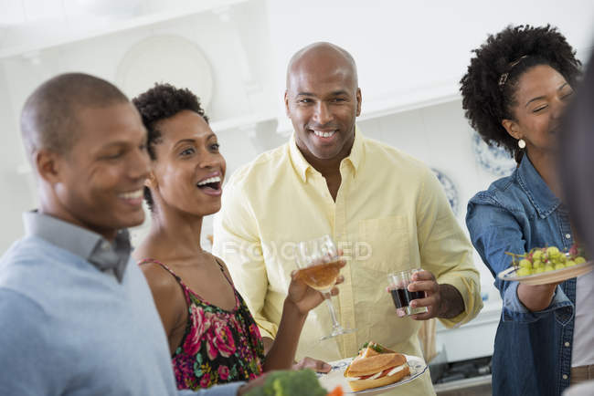 Small group of people holding drinks at indoor party. — Stock Photo