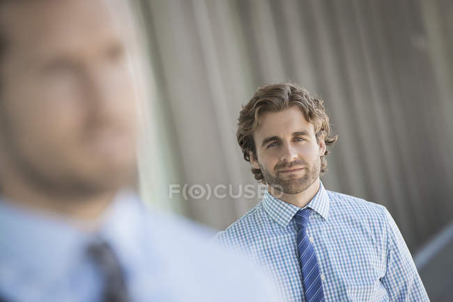 Двое мужчин, стоя на улице с упором на фоне — стоковое фото