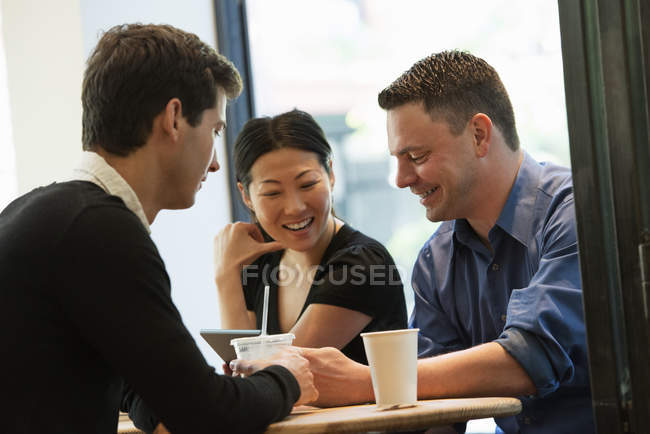 Group of people sitting around table in coffee shop with drinks and looking at digital tablet. — Stock Photo
