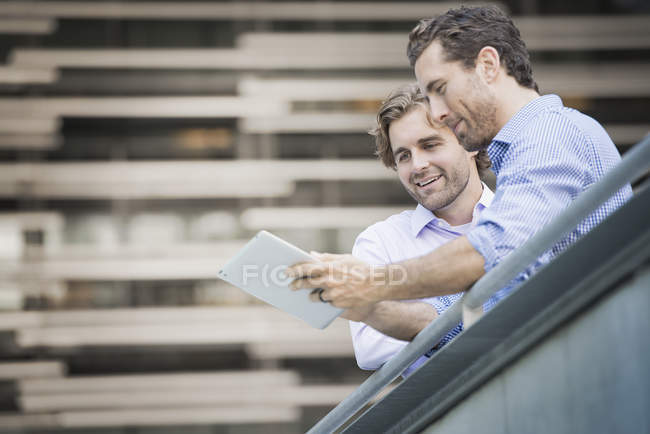 Two men standing on urban walkway and looking at digital tablet, low angle view. — Stock Photo